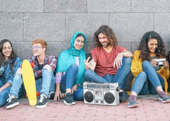Group of diverse friends having fun outdoor - Millennial young people using mobile phones taking photo and listening music with vintage stereo - Generation z, social media and youth lifestyle concept