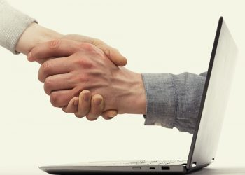 A deal between two partners from the laptop. Modern technology in business.