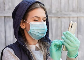 Young woman with mask and gloves having a video conference, working at home  - covid-19 pandemic